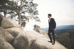 Den ursnygga bruden, ansar att kyssa och att krama nära klipporna med att bedöva sikter Royaltyfri Foto