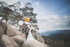 Den ursnygga bruden, ansar att kyssa och att krama nära klipporna med att bedöva sikter Royaltyfri Fotografi