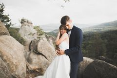 Den ursnygga bruden, ansar att kyssa och att krama nära klipporna med att bedöva sikter Arkivbild