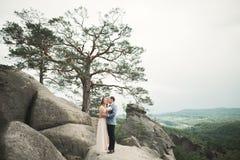 Den ursnygga bruden, ansar att kyssa och att krama nära klipporna med att bedöva sikter arkivfoto