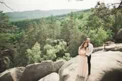 Den ursnygga bruden, ansar att kyssa och att krama nära klipporna med att bedöva sikter arkivbilder
