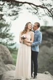 Den ursnygga bruden, ansar att kyssa och att krama nära klipporna med att bedöva sikter arkivfoton