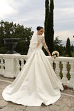 Den ursnygga bruden med mörkt hår bär den eleganta bröllopsklänningen Royaltyfri Foto