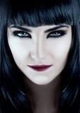 Den ursnygga brunetten med mörk makeup och vit flår Fotografering för Bildbyråer