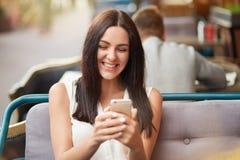 Den ursnygga brunettkvinnlign med lyckligt uttryck, läser några angenäma kommentarer under hennes foto i sociala nätverk, använde arkivbilder