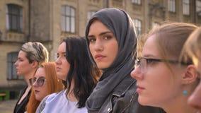 Den ursnygga caucasian flickan i hijab ser exakt från gruppen av utomhus- olika kvinnor stock video
