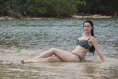 Den ursnygga flickan i en bikini är i vattnet i sanden Arkivbilder