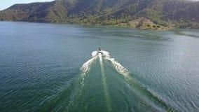 Den ursnygga flyg- sikten för surret 4k på personvattenskidåkning fäste till det motoriska fartyget i tropisk seascape för havber arkivfilmer
