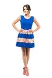 Den ursnygga gulliga flickan i anseende för sommarblåttklänning med korsade ben och akimbo poserar Arkivfoton