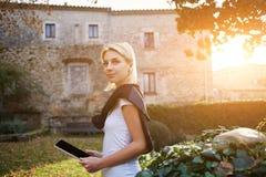Den ursnygga kvinnaluffaren är den hållande digitala minnestavlan och att tycka om henne som går i okänd stad Arkivfoto