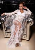Den ursnygga kvinnan bär den eleganta klänningen som poserar i lyxig inre Arkivbilder