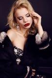 Den ursnygga kvinnan med blont hår bär den lyxiga klänningen, päls och smycket Arkivfoto