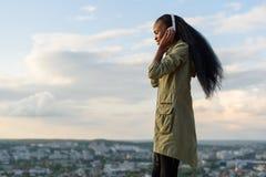 Den ursnygga le afrikansk amerikanflickan lyssnar musik och att koppla av Suddig cityscapebakgrund utomhus- stående Royaltyfri Foto