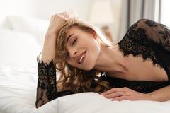 Den ursnygga le brunettkvinnan ligger på säng Arkivbilder