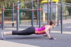 Den ursnygga slanka unga kvinnan i konditionaktivitet på utomhus- sportsground, skjuter ups och ner Morgonutbildning för verklig  arkivbilder