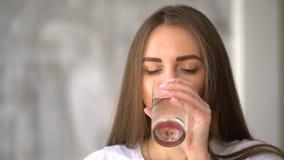Den ursnygga unga flickan håller sunt, genom att dricka ett exponeringsglas av vatten inomhus och att le flickadricksvatten från  stock video