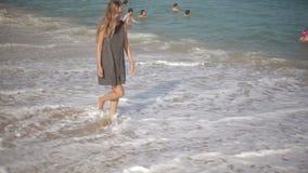 Den ursnygga unga flickan med ett härligt diagram som poserar och, promenerar kusten arkivfilmer