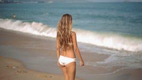 Den ursnygga unga flickan med ett härligt diagram som poserar och, promenerar kusten lager videofilmer