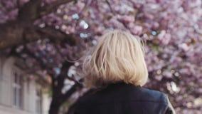 Den ursnygga unga kvinnan i en stilfull dräkt som har gyckel i den körsbärsröda blomstra staden, går, hoppar och skrattar lycklig lager videofilmer