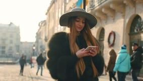 Den ursnygga unga kvinnan i ett ljust solljus använder hennes telefon, medan stå i centret arkivfilmer