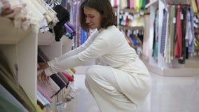 Den ursnygga unga kvinnan i textil shoppar med en variation av silkespapper på bakgrunden Kunden avgör vilken typ av arkivfilmer