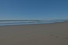 Den ursprungliga stranden med slätt blöter sand Arkivfoton