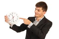 Den utövande mannen indikerar till klockan royaltyfria foton