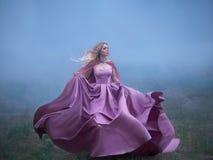 Den utmärkta mystiska blonda damen kör i väg från en mardröm, ett skogmonster, hennes ljusa långa dyra kungliga klänning royaltyfria foton