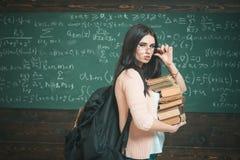 Den utmärkta studenten ackumulerar kunskap Flickan med stora ryggsäckhåll traver böcker, svart tavlabakgrund Flickastudent royaltyfri fotografi