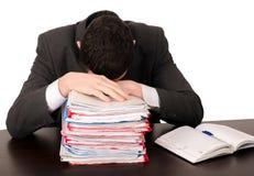 Trött affärsman som sovar på arbete. Arkivbild