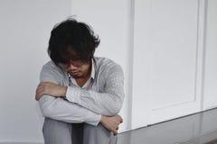 Den utmattade trötta asiatiska affärsmannen sitter och kramar hans knä på det utvändiga kontoret Royaltyfria Foton