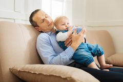 Den utmattade uppmärksamma fadern som sovande faller, medan ge vatten till hans, behandla som ett barn Arkivfoton