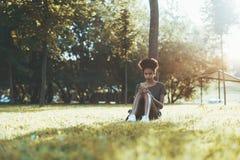 Den utomhus- afro- flickan parkerar in att prata via mobiltelefonen royaltyfria bilder