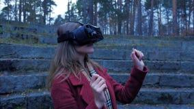 Den utomhus- blonda flickan har gyckel i VR-exponeringsglas Tonåringflicka som tycker om virtuell verklighetexponeringsglas som ä Arkivfoton