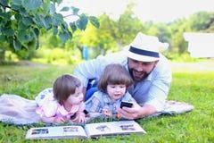 Den utomhus- familjen lägger gräs royaltyfri foto