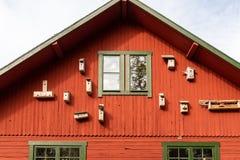 Den utomhus- främre sikten av många fågelredet boxas på den röda yttre träbyggnadsväggen med fönster arkivbild