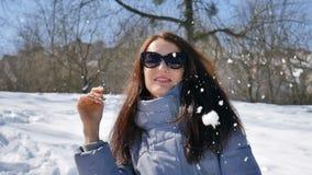 Den utomhus kvinnliga ståenden av den härliga vuxna flickan i mörk solglasögon som att spela kastar snöboll på bakgrund för blå h lager videofilmer
