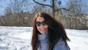 Den utomhus kvinnliga ståenden av den unga aktiva kvinnan i mörk solglasögon som att spela kastar snöboll på bakgrund för blå him lager videofilmer
