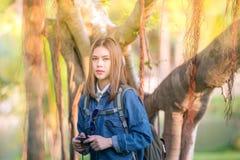 Den utomhus- modeståendehandelsresanden av den hållande kameran för den stilfulla fotografflickan, bärande jeans klår upp, moderi Arkivbild