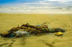 Den utomhus- sikten av fisknät- och repavskräde i stranden, varje dagavfalls ackumulerar på stranden från havströmmar arkivbild