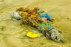 Den utomhus- sikten av fisknät- och repavskräde i stranden, varje dagavfalls ackumulerar på stranden från havströmmar fotografering för bildbyråer