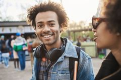 Den utomhus- ståenden av den charmiga afrikansk amerikanmannen som går med vännen parkerar in och att bära grov bomullstvillkläde royaltyfria foton
