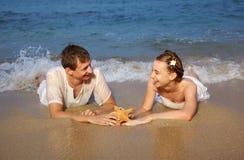 Romantiker kopplar ihop på stranden Arkivfoto