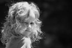 Den utomhus- ståenden av en gullig liten flicka med lockigt hör och att se tillbaka över hennes skuldra svart white Arkivbild