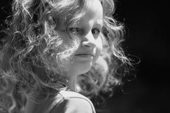 Den utomhus- ståenden av en gullig liten flicka med lockigt hör och att se tillbaka över hennes skuldra svart white Royaltyfria Foton
