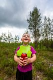Den utomhus- ståenden av en lycklig le pys som bär en haklapp och rymmer en röd sodavatten kan Skognaturplats royaltyfria bilder