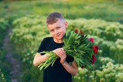 Den utomhus- ståenden av en pojke på går med pionblommor royaltyfri foto