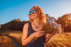 Den utomhus- ståenden av den härliga unga kvinnan med det röda innehavet för lockigt hår blommar Kopiera utrymme Royaltyfri Foto