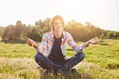 Den utomhus- ståenden av teengersammanträde på korsat grönt gräs räcker att stänga hans ögon som mediterar att försöka att koppla royaltyfri bild