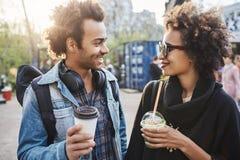 Den utomhus- ståenden av två gulliga afrikansk amerikanpersoner som omkring hänger, parkerar och att dricka kaffe, att skratta oc royaltyfria bilder